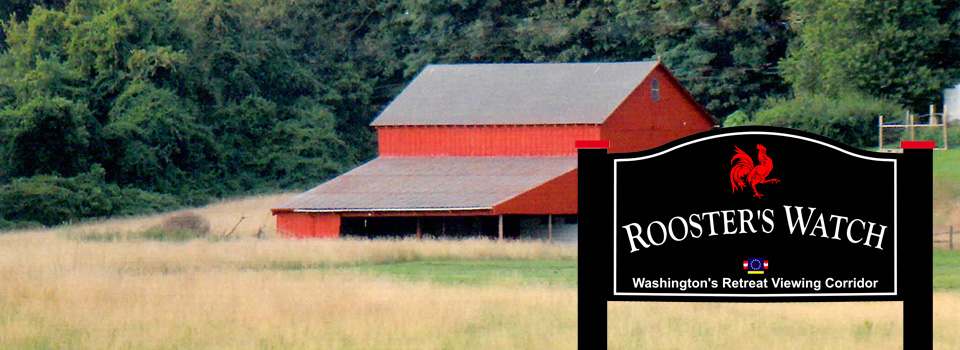 A large field with a barn and house in the distance. Rooster's Watch Sign.